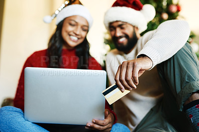 Buy stock photo Shot of a happy young couple using a laptop and credit card during Christmas at home