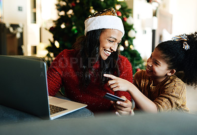 Buy stock photo Shot of a young woman using a laptop and credit card with her daughter during Christmas at home