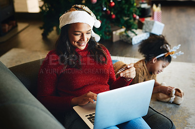 Buy stock photo Shot of a young woman using a laptop and credit card with her daughter playing in the background during Christmas at home