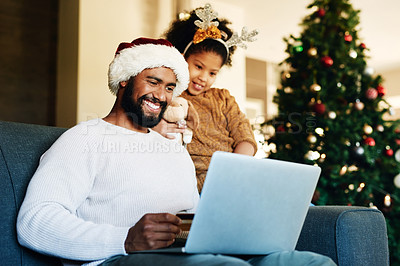 Buy stock photo Shot of a young man using a laptop and credit card with his daughter during Christmas at home