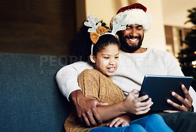 Buy stock photo Shot of a happy young father and daughter using a digital tablet on the sofa during Christmas at home