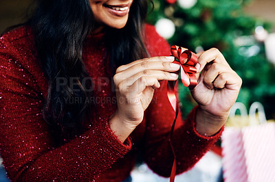 Buy stock photo Shot of an unrecognisable woman wrapping a Christmas gift at home