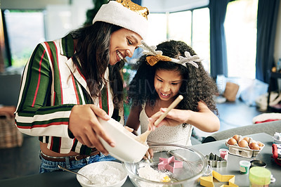 Buy stock photo Shot of a happy young mother and daughter preparing a meal during Christmas at home