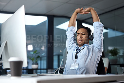 Buy stock photo Shot of a young man stretching while using a headset and computer in a modern office