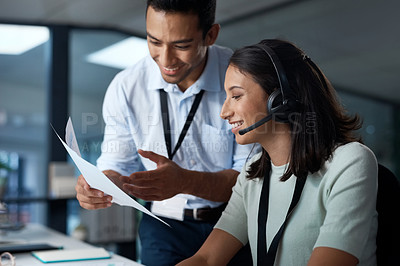 Buy stock photo Shot of a young man and woman reading a document while working in a call centre
