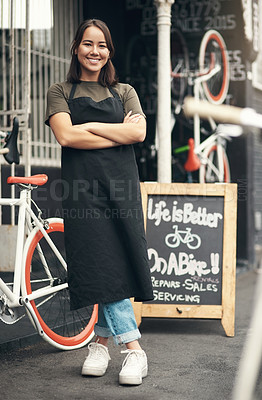 Buy stock photo Full length shot of an attractive young woman standing outside her bicycle shop with her arms folded