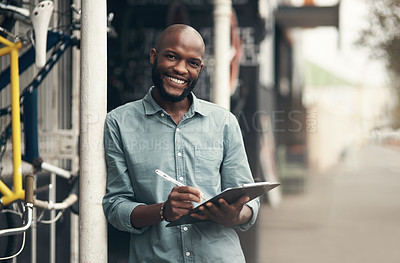 Buy stock photo Shot of a handsome young man standing alone outside his bicycle shop and writing on a clipboard