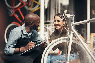 Buy stock photo Shot of a handsome young man crouching outside his bicycle shop and assisting a customer