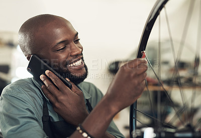 Buy stock photo Shot of a handsome young man standing alone in his shop and repairing a bicycle wheel while using his cellphone