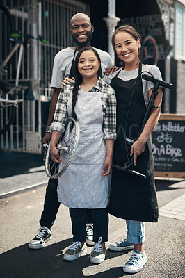 Buy stock photo Portrait of three young workers standing in front of their bicycle repair shop outside