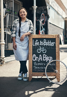 Buy stock photo Portrait of a young woman leaning on a bicycle repair shop sign outside
