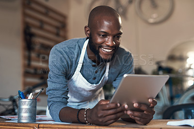 Buy stock photo Shot of a young man using a digital tablet at work