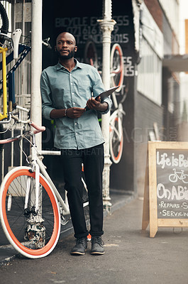 Buy stock photo Full length shot of a handsome young man standing outside his bicycle shop and looking contemplative while holding a clipboard