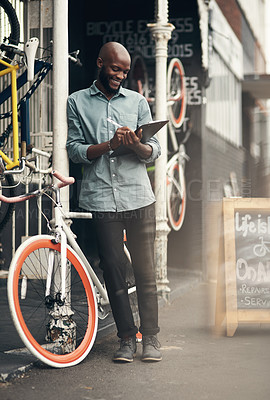 Buy stock photo Full length shot of a handsome young man standing alone outside his bicycle shop and writing on a clipboard