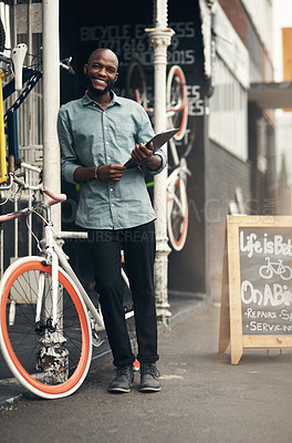 Buy stock photo Full length shot of a handsome young man standing alone outside his bicycle shop and holding a clipboard