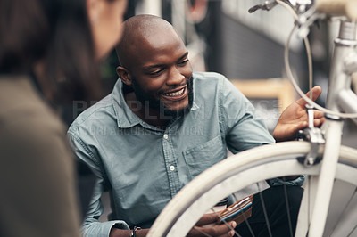 Buy stock photo Shot of a handsome young man crouching down and looking at a bicycle before buying it