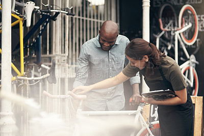Buy stock photo Shot of an attractive young woman standing outside her bicycle shop and assisting a customer