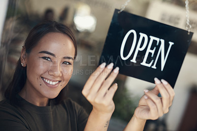Buy stock photo Shot of an attractive young woman standing and turning the sign on the door to her bicycle shop