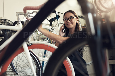 Buy stock photo Shot of an attractive young woman crouching down in her bicycle shop and using her cellphone
