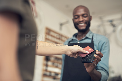 Buy stock photo Shot of a handsome young man standing in his bicycle shop and assisting a customer with her purchase