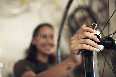 Buy stock photo Shot of an unrecognizable woman standing alone in her shop and repairing a bicycle wheel