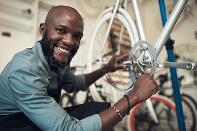 Buy stock photo Shot of a handsome young man crouching in his shop and repairing a bicycle wheel