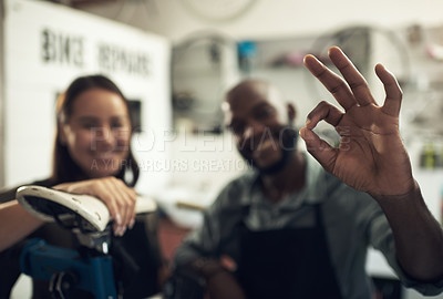 Buy stock photo Shot of two unrecognizable business owners standing together in their bicycle shop and making an okay hand gesture