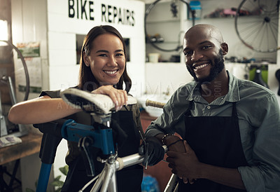 Buy stock photo Shot of two young business owners standing together in their bicycle shop during the day