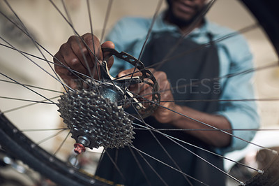Buy stock photo Low angle shot of an unrecognizable man standing alone in his shop and repairing a bicycle wheel