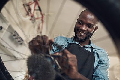 Buy stock photo Low angle shot of a handsome young man standing alone in his shop and repairing a bicycle wheel