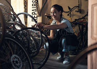 Buy stock photo Shot of a young happy young woman fixing a bike at a bicycle repair shop