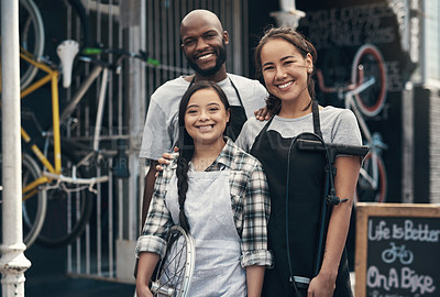 Buy stock photo Portrait of three young colleagues standing outside their bicycle repair shop