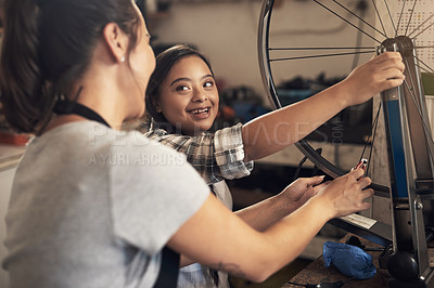 Buy stock photo Shot of two young female  workers fixing a bike at a bicycle repair shop