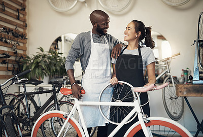 Buy stock photo Shot of two colleagues bonding while holding onto a bicycle wheel at a bicycle repair shop
