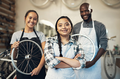Buy stock photo Portrait of three young colleagues working together at a bicycle repair shop