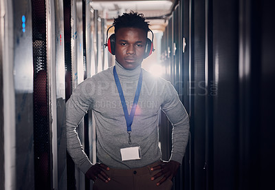 Buy stock photo Portrait of a young handsome man wearing headphones in a server room at work