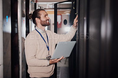Buy stock photo Shot of a young man using a laptop in a server room at work