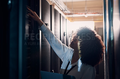 Buy stock photo Shot of a young woman at work in a server room