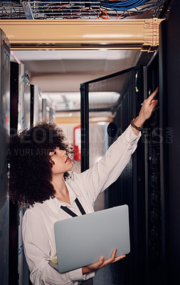 Buy stock photo Shot of a young woman holding a laptop in a server room at work