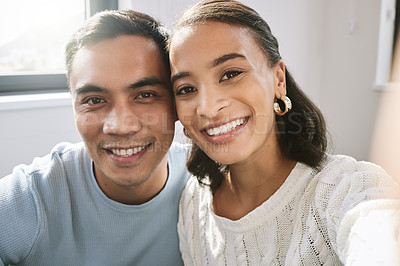 Buy stock photo Shot of a young couple sitting together and taking a selfie in their new home