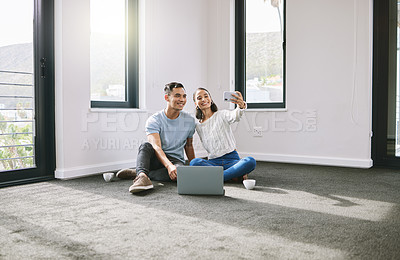 Buy stock photo Full length shot of a young couple sitting together and using a cellphone to take selfies in their new home