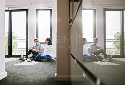 Buy stock photo Full length shot of a young couple sitting on the floor together in the new house and using a laptop