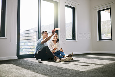 Buy stock photo Full length shot of a young couple sitting together and planning the interior design of their new home