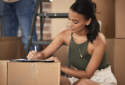 Buy stock photo Shot of a young woman signing a contract at home