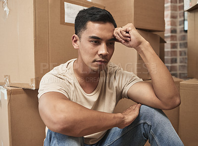 Buy stock photo Shot of a young man being upset while sitting on the floor at home