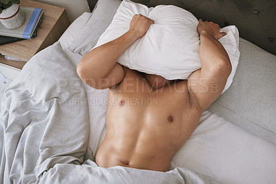 Buy stock photo High angle shot of an unrecognizable young man lying in bed with his pillow over his head