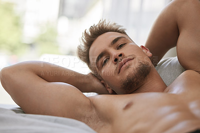 Buy stock photo Cropped portrait of a handsome and muscular young man lying in his bed at home