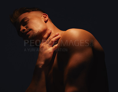 Buy stock photo Shot of a handsome young man with no shirt on standing in the shadows