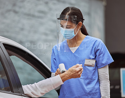Buy stock photo Shot of a young healthcare worker taking a patient's temperature at a drive through vaccination site