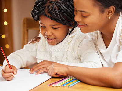 Buy stock photo Shot of a young mother and daughter doing homework together at home